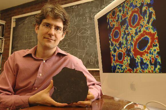 Charles Kevin Boyce laiko nuo Prototaxites nupjautą plokštelę. Kompiuterio ekrane stipriai išdidintas organizmo ląstelės cheminis žemėlapis (Lloyd DeGrane)